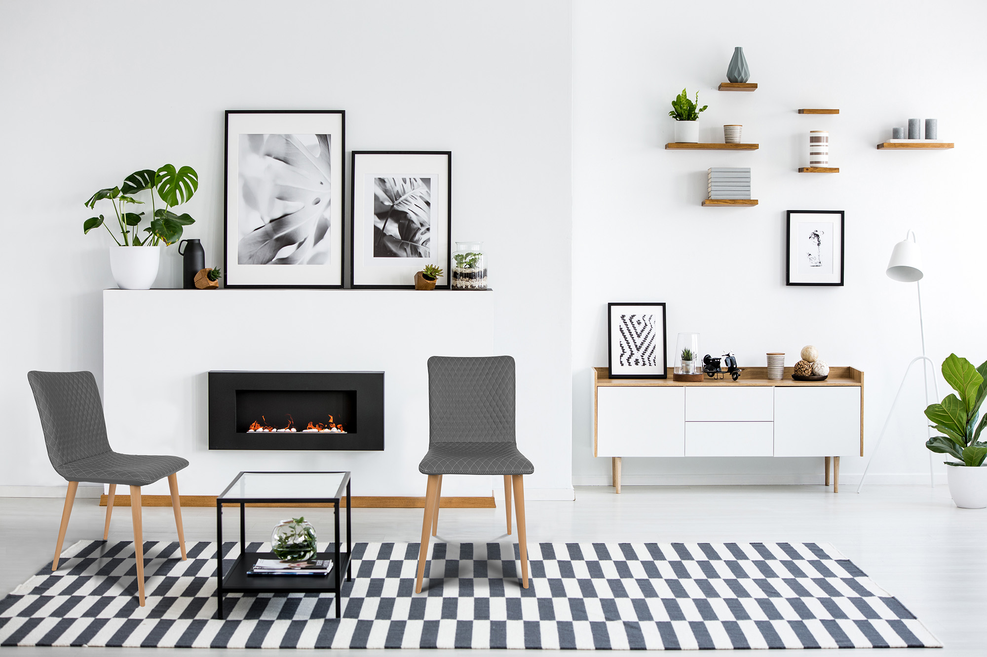 Fireplace between grey armchairs in modern living room interior with posters and plants. Real photo